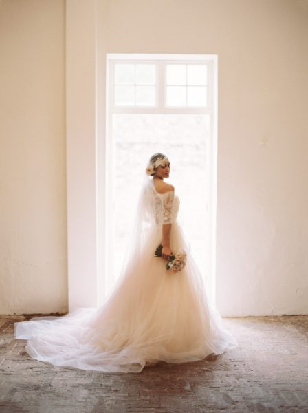 Bignor Park shoot featuring a Bride standing in a doorway wearing a Blush tulle dreamy JLM, Tara Keely wedding dress
