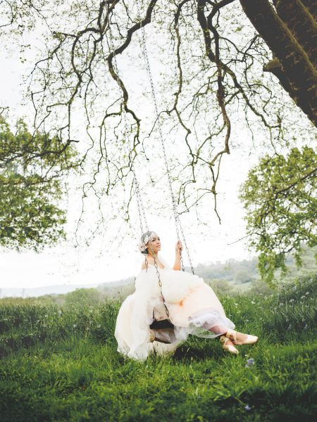 Fine Art Bignor Park shoot featuring a Bride wearing a Blush tulle dreamy JLM, Tara Keely wedding dress swinging on a swing suspended from a large dramatic tree