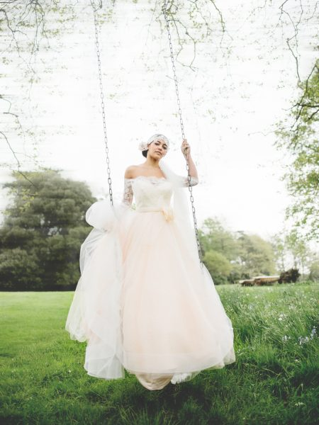 Fine Art Bignor Park shoot featuring a Bride wearing a Blush tulle dreamy JLM, Tara Keely wedding dress swinging on a swing suspended from a tree