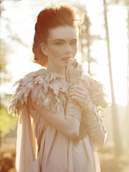 Dreamy forest nymph shoot in the New Forest featuring a red headed model looking whimsically at camera wearing a gold tipped feather bolero and nude dress set against an Autumnal golden forest