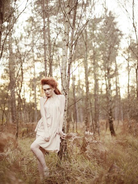 Dreamy forest nymph shoot in the New Forest featuring red headed model looking whimsically at camera leaning against tree wearing nude dress set against an Autumnal golden forest