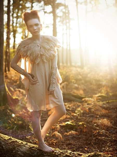 Dreamy forest nymph shoot in the New Forest featuring red headed model looking whimsical standing on a tree trunk wearing a gold tipped feather bolero and nude dress set against an Autumnal golden forest