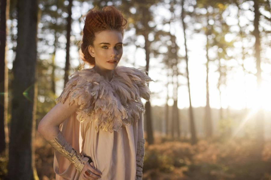 Dreamy forest nymph shoot in the New Forest featuring a red headed model looking directly to camera wearing a gold tipped feather bolero and nude dress set against an Autumnal golden forest