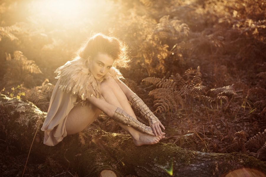 Dreamy forest nymph shoot in the New Forest featuring a red headedmodel looking whimsical sitting hunched on a tree trunk wearing a gold tipped feather bolero and nude dress set against an Autumnal golden forest