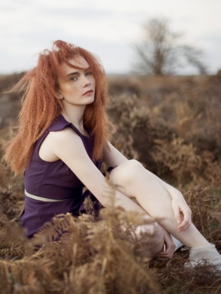 Dreamy forest nymph shoot in the New Forest featuring close up of red headed model in golden bracken wearing a purple indigo dress dress set against an Autumnal golden heathland