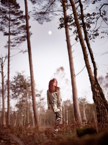 Dreamy forest nymph shoot in the New Forest featuring a red headed model standing between tall pine trees and moon
