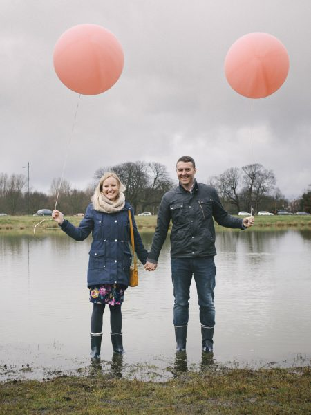 Love shoot engagement shoot couple standing in front of pond in rainwear holding two pink blush balloons on Wimbledon Common London