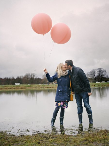 Love shoot engagement shoot couple standing in front of pond in rainwear kissing while holding two pink blush balloons on Wimbledon Common London