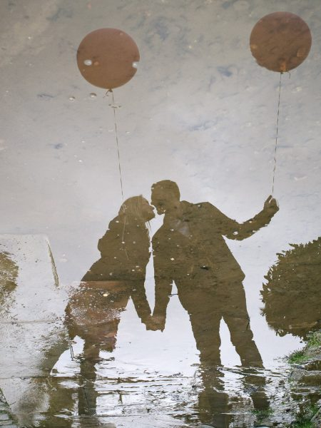 Reflection of a Love shoot engagement shoot couple standing in front of pond in rainwear holding two pink blush balloons on Wimbledon Common London
