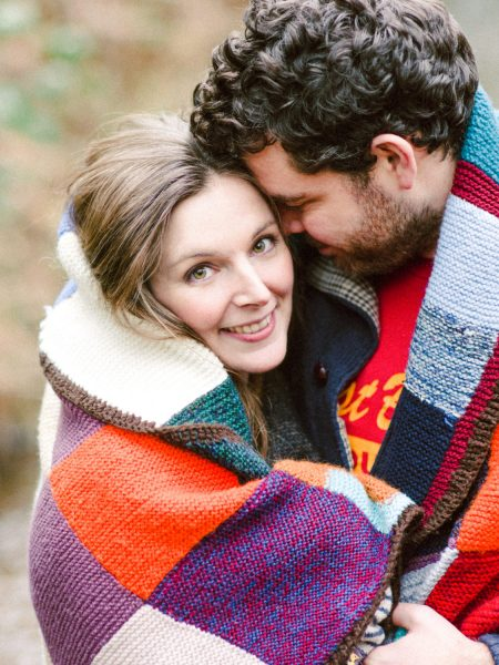 Engagement shoot LOVE couple snuggled up under orange and purple multicoloured blanket rug London