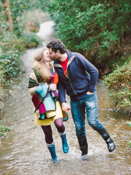 Engagement shoot LOVE couple kissing while running in a stream under orange and purple multicoloured blanket rug London