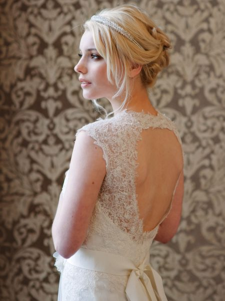 Nonsuch manor Katie Elizabeth of London headpiece shoot featuring side on view of blonde model set against a damask wallpaper