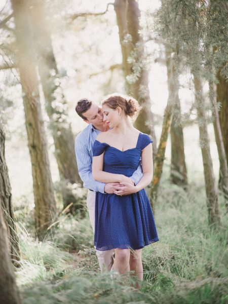 Fine Art engagement shoot of a Groom to be hugging Bride with Bride standing in front against a backdrop of woodland in Ashdown forest