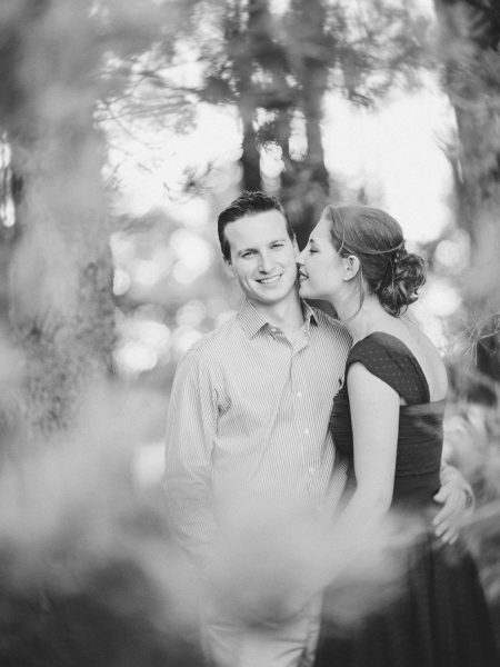 Fine Art Black and White image of engagement shoot of a Groom to be looking at camera while Bride to be nuzzles his face Ashdown forest