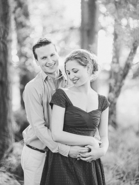 Fine Art engagement shoot of a Groom hugging Bride to be with Bride to be standing in front against a backdrop of woodland in Ashdown forest