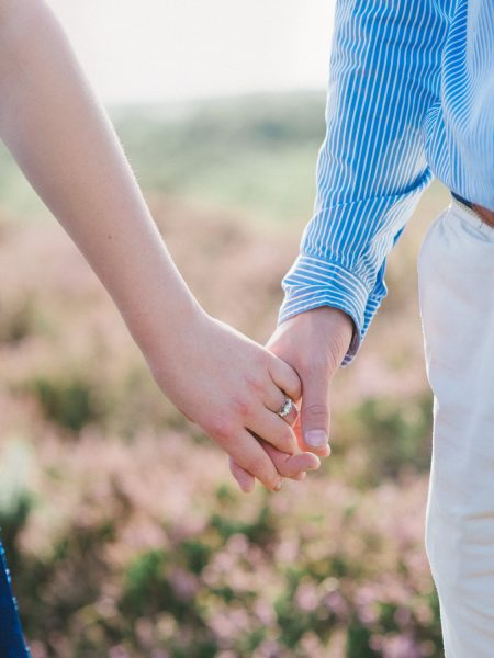 Fine Art engagement shoot of close up of hands holding hands against a backdrop of heather heath in Ashdown forest