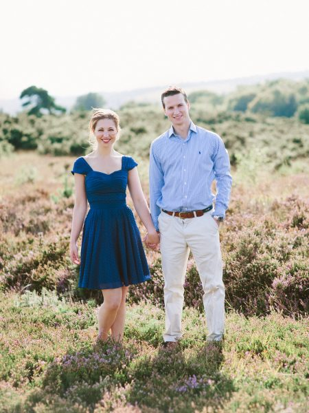 Fine Art engagement shoot of couple looking at camera against a backdrop of heather heath in Ashdown forest