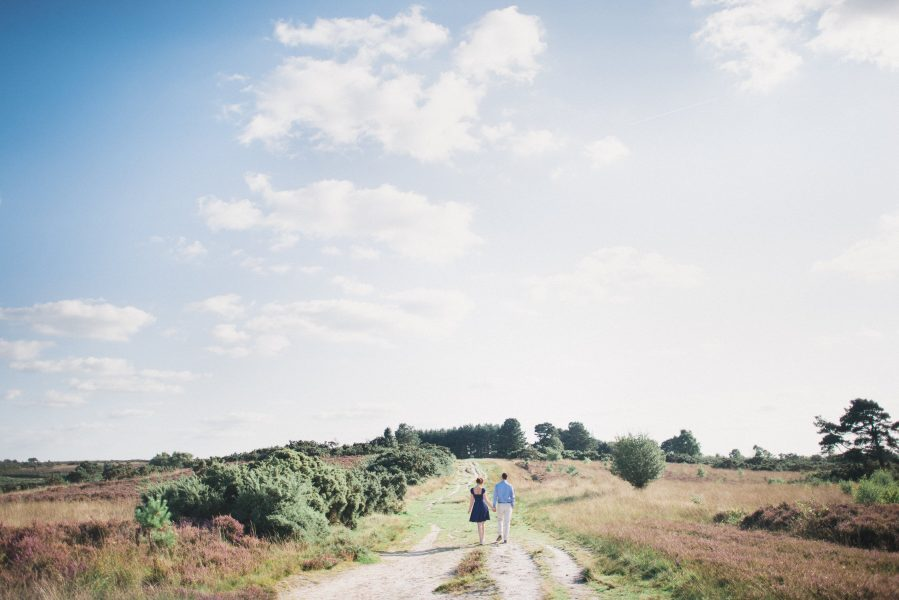 Fine Art engagement shoot of a couple walking into the distance against a backdrop of heather heath in Ashdown forest