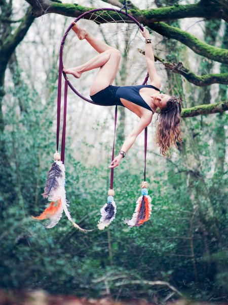 New Forest Dream Catcher shoot model in black leotard sitting in hoop decorated with dangling feathers suspended high in air off a tree