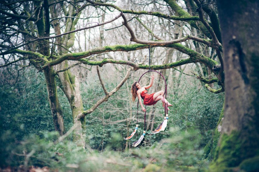 New Forest Dream Catcher shoot model in an orange dress sitting in hoop decorated with dangling feathers suspended high in air off a tree