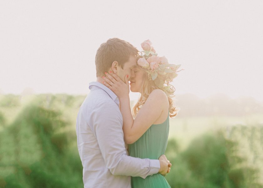 Fine Art engagement shoot couple kissing. Girl in a floral garland and green dress, boy in blue shirt