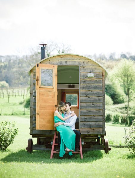Fine Art engagement shoot couple sitting on the stairs of a shepherds hut. Girl in a green dress sitting on lap of Fiancé,