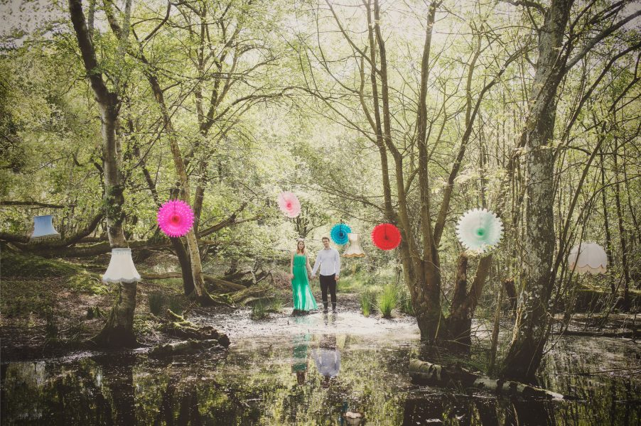 Fine Art engagement of girl in green dress holding Fiancé's hand in front of a dramatic woodland bog with brightly coloured paper decorations