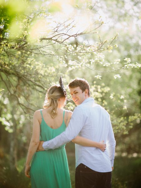Fine Art engagement in woodland featuring back view of girl in a green dress with arm around Fiancé's waist