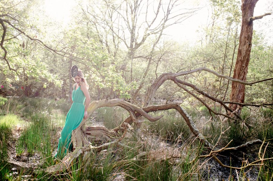 Fine Art engagement in woodland featuring girl in a green dress leaning on a dramatic fallen tree in magical sunlight
