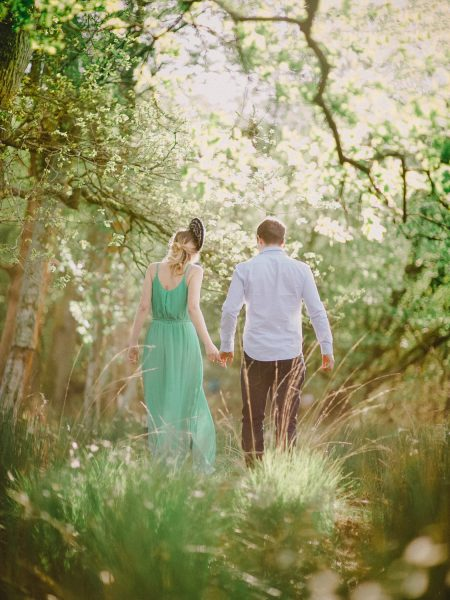 Fine Art engagement shoot in woodland featuring girl in a long green dress walking with Fiancé in magical sunlight
