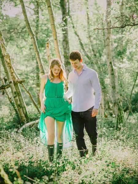 Fine Art engagement shoot in woodland featuring girl in a long green kissing Fiancé in magical sunlight