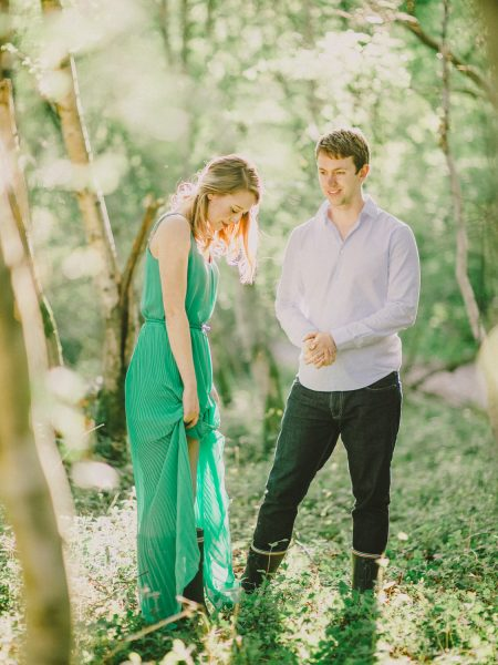 Fine Art engagement shoot in woodland featuring girl in a long green standing in a relaxed style with her Fiancé in magical sunlight