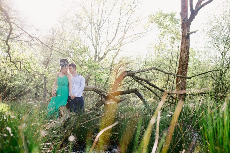 Fine Art engagement in woodland featuring girl in a green dress and Fiancé leaning on a dramatic fallen tree in magical sunlight
