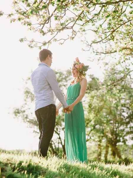 Fine Art engagement in apple blossom ancient orchard featuring girl in a green dress and floral garland and Fiancé in magical sunlight