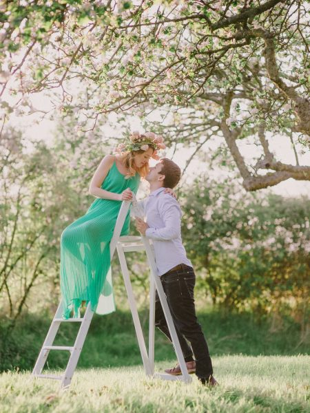 Fine Art engagement in apple blossom ancient orchard featuring girl in a green dress and floral garland sitting on step ladder chatting with her Fiancé in magical sunlight