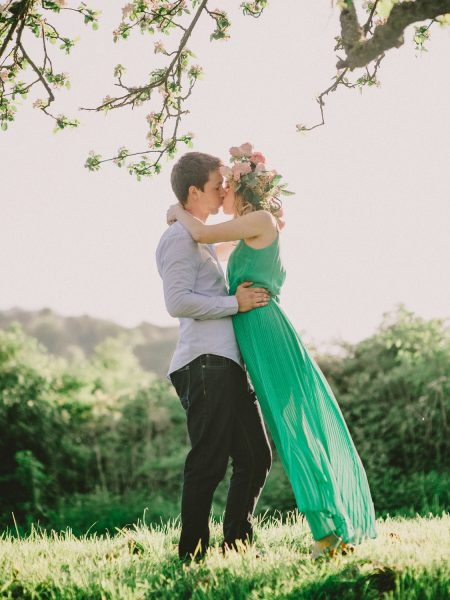 Fine Art engagement in apple blossom ancient orchard featuring girl in a green dress and floral garland and Fiancé kissing in magical sunlight