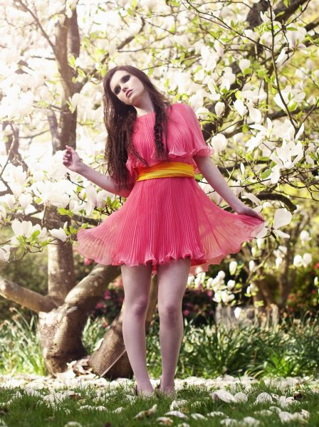 Japanese The Tale of Genji fashion shoot of girl in a coral pleated dress in front of a beautiful magnolia tree with sunlight filtering through
