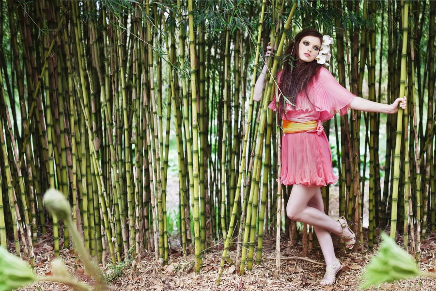 Japanese The Tale of Genji fashion shoot of girl in a coral pleated dress in front of a backdrop of bamboo