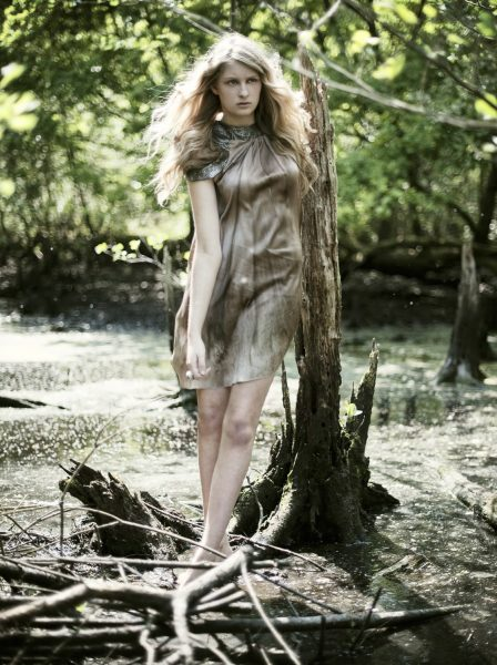 Princess Vasillissa Russian fairytale and The Firebird inspired fashion shoot of model with long blonde hair wearing a graduated brown dress standing on a tree stump in a dramatic bog