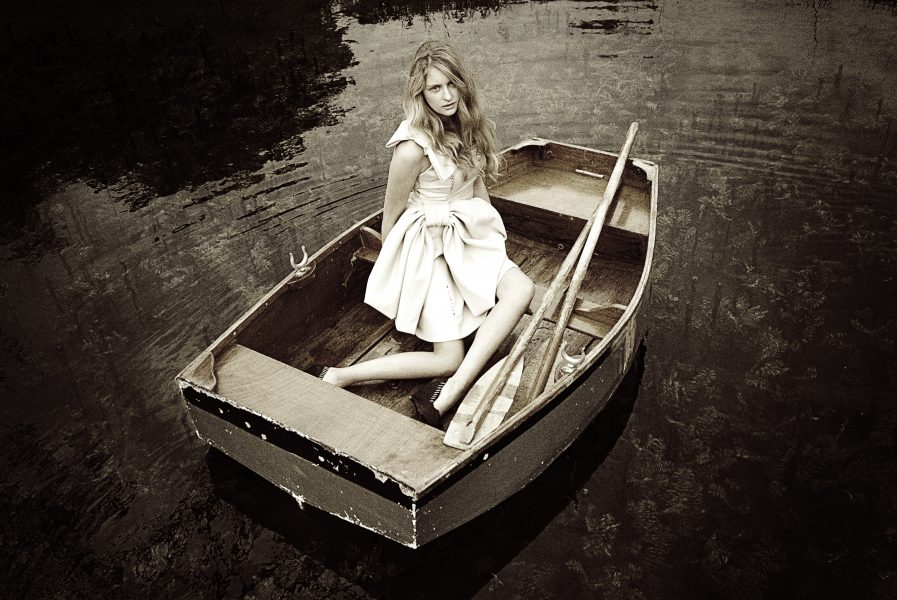 Princess Vasillissa and The Firebird Russian fairytale inspired fashion shoot of model with long blonde hair sitting in a rowing boat wearing a cream dress gazing at camera
