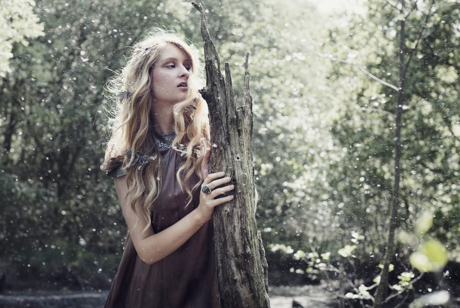 Princess Vasillissa Russian fairytale and The Firebird inspired fashion shoot of model with long blonde hair wearing a graduated brown dress holding a tree stump in a dramatic bog with tree seed floating in the air like magic