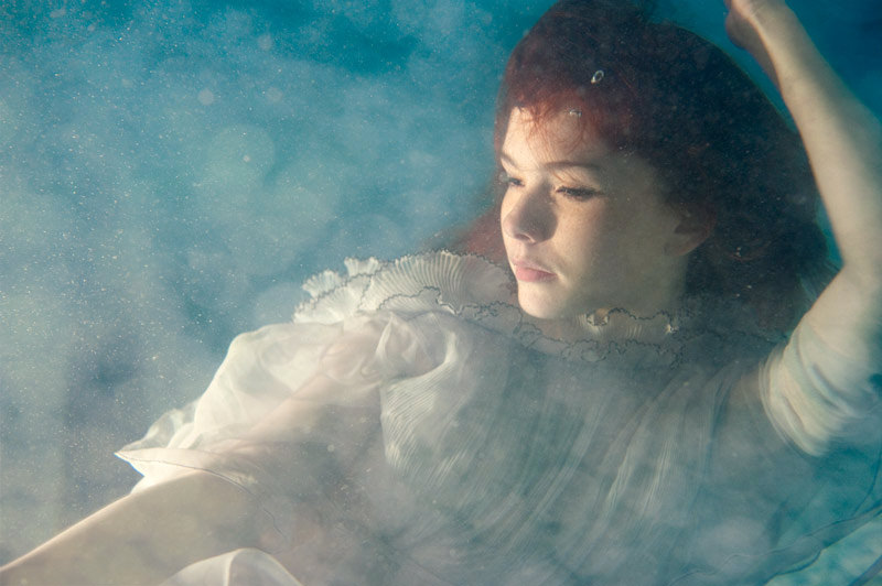 Under water fashion shoot of girl with red hair in a floaty pale blue dress looking dreamily to the side