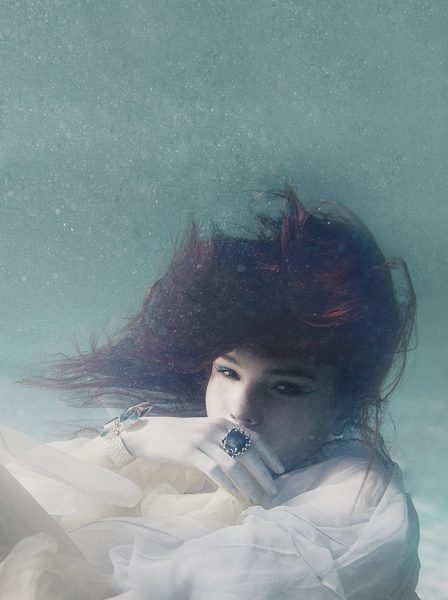 Under water fashion shoot of girl with red hair in a floaty pale blue dress looking dreamily to the side showing off a ring