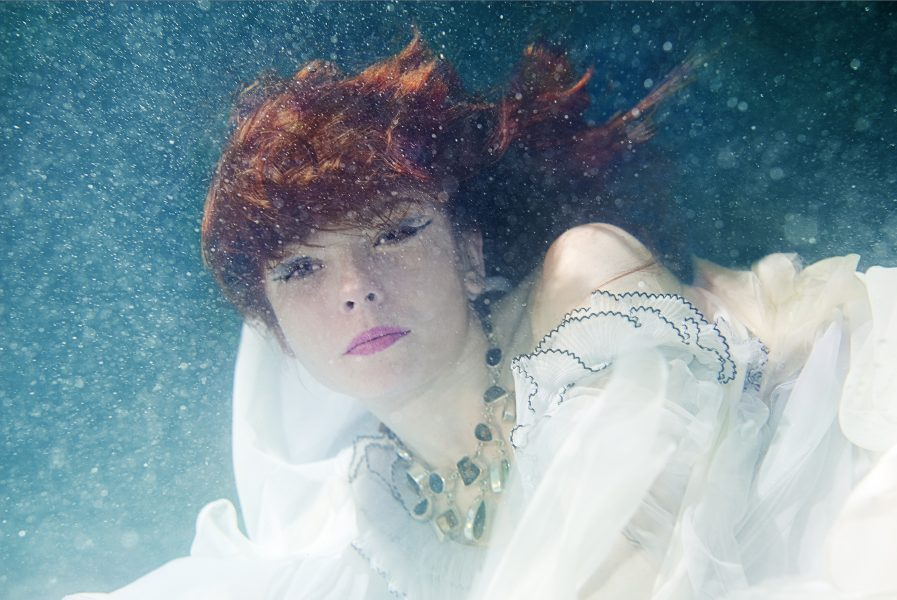 Under water fashion shoot of girl with red hair in a floaty pale blue dress looking dreamily at the camera
