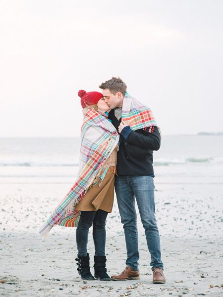 Engagement LOVE shoot in Winter couple cuddling and kissing under a check rug blanket on a blustery West Wittering Beach West Sussex