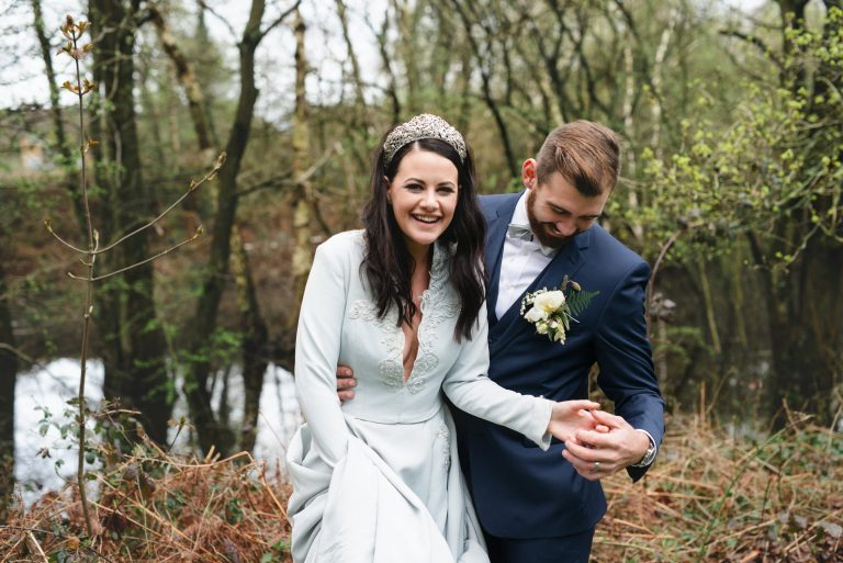 Bride in blue wedding dress smiles while Groom in modern wedding suit holds her hand in front of rustic Hampshire lake