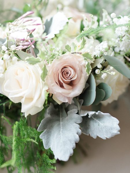Close up of bouquet of soft dusky pink roses, creams, ferns anemones and blush rustic flowers.