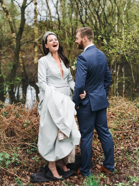 Bride in blue wedding dress laughing with Groom in front of rustic Hampshire lake