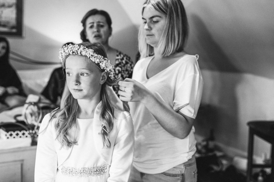 Stylist putting floral hair crown on Flower girl in Hampshire
