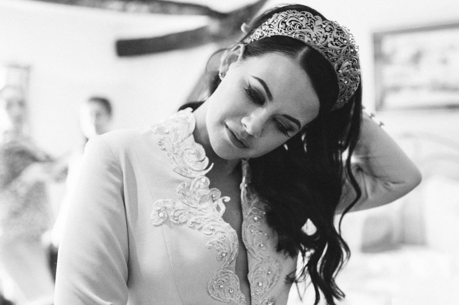 Bride in modern wedding crown holding arm behind head as looks down in a candid moment of pre wedding excitement